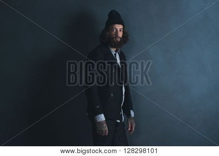 Retro 1970S Beard Man With Long Hair Wearing Black Coat And Woolen Cap. Standing Against Gray Wall.