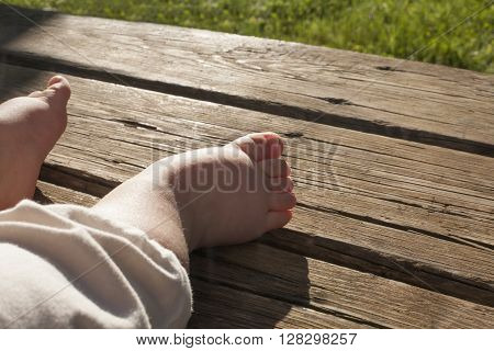 Bare feet of a male baby over weathered wooden background. Natural light