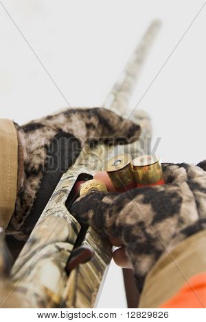 Gloved hands loading shell into shotgun.