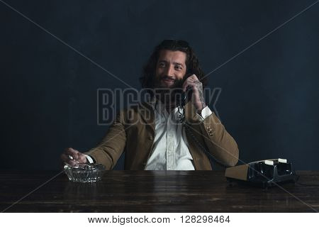 Smiling Retro 1970 Undercover Agent With Beard Calling Behind Desk While Smoking Cigarette.