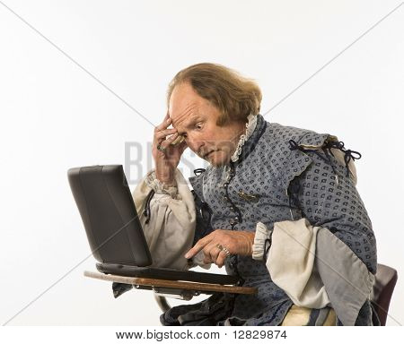 William Shakespeare in period clothing sitting in school desk with laptop computer and hand to head looking perplexed.