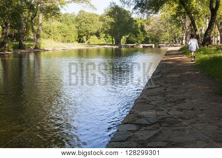 Toddler girl taking a walk all alone by La Codosera Natural Pools Badajoz Spain