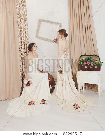 Wedding dress fashion. Two beautiful young brides in vintage wedding dresses indoors. Rustic wedding dresses at models. Girls in champaigne color dresses in decorated interior with flowers, high key.