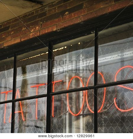 Neon sign in window for tattoos and body piercing.
