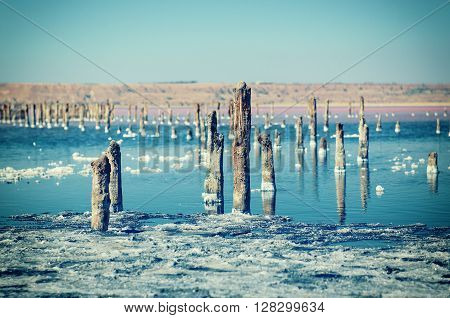 Beautiful salt lake with blue and pink water and wooden posts, natural landscape amazing vintage background