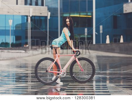 Sexy girl with bicycle. Young slim sexy sportive woman in blue shorts and white snickers long-haired, sensual posing with pink fix bicycle in urban city enviroment. Soft toned.