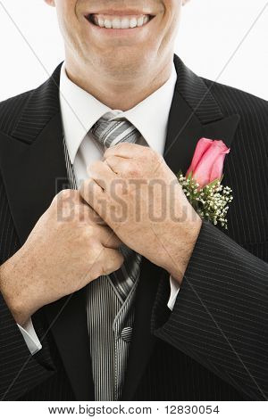 Close up of Caucasian groom adjusting his tie.