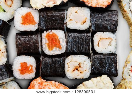 Japanese food background - sushi maki gunkan salmon roll isolated at white background, above view. Closeup detail of sushi rolls. Sushi set macro close up.