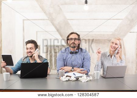 Business people communicating over mobile phones in office. Happy people solving problems with business partners.