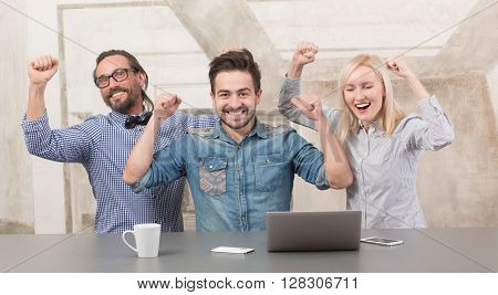 Business people expressing success while working in office. Happy people raising hands and laughing all together.