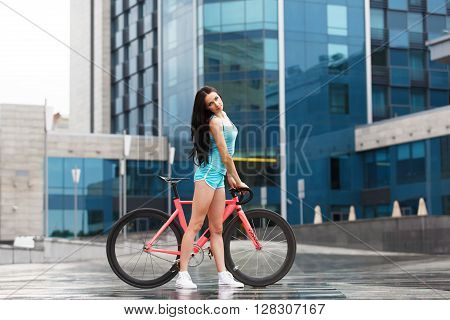 Sexy girl with bicycle. Young slim sexy sporty woman in blue shorts and white snickers long-haired, sensual posing with pink fix bicycle in urban city environment. Soft toned.