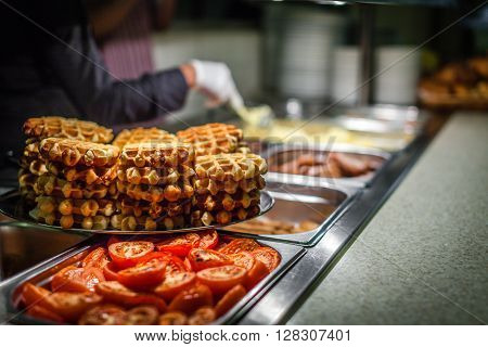 Hot counter containing warm breakfast items such as scrambled or fried tomatoes, waffles, bacon, sausages and others in a self service restaurant in a hotel