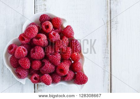 Fresh raspberries in bowl on wooden background