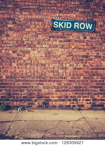 Urban Decay Image Of A Skid Row Sign On A Red Brick Wall