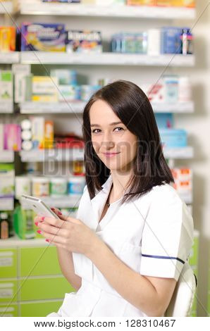 Young pharmacist woman using a app on a smart phone Pharmaceutical background. Drugstore. Pills and medicine