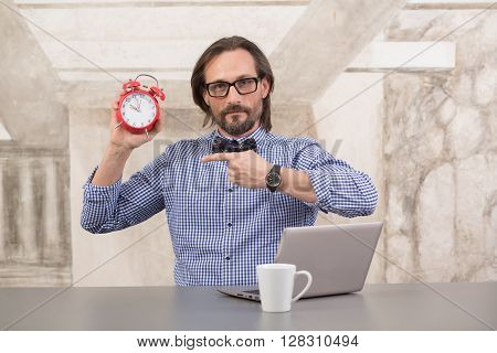 Businessman holding alarmclock demonstrating that it is time for work or rest. Handsome man in glasses sitting in front of computer in office.