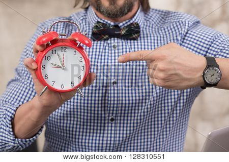 Close-up picture of businessman holding red-coloured alarmclock showing that it it time for rest after hard working day.