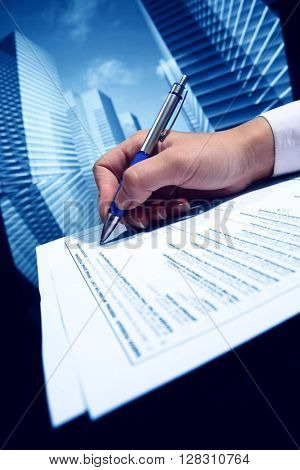 Businessman signing a document on futuristic skyscrapers background