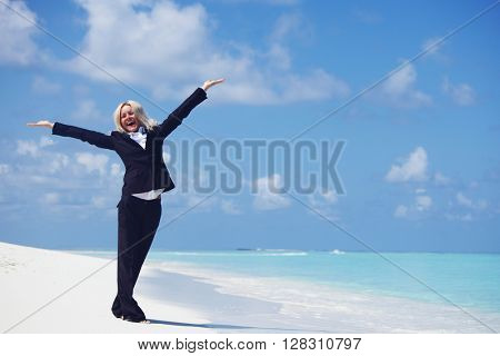 Business woman with raised hands on ocean beach