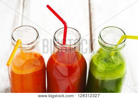 Fruits and vegetable juice in bottle: Apple and spinach juice Carrot juice and Tomato juice.