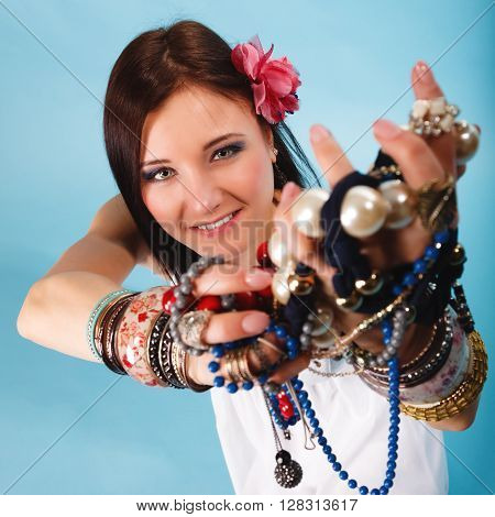 Beauty young woman in summer style with plenty of jewellery beads in hands blue background
