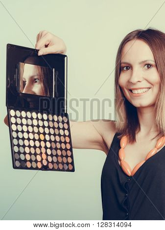 Woman stylist holding professional eyeshadow makeup palette with mirror. Beautyfying eye eyelid. Make up makeover concept.