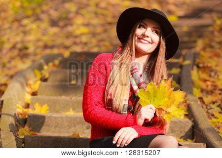 Portrait of attractive young smiling woman holding big gold leafs in autumnal park. Fashionable girl wearing red sweater scarf and black hat.