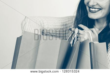 Happy girl on christmas shopping. Young cheerful woman with bags wearing santa cap. Holidays celebration commerce happiness leisure concept.
