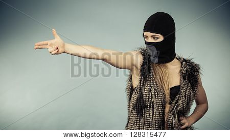 Woman sexy girl in balaclava black bra lingerie making gun gesture. Crime and violence on blue studio shot