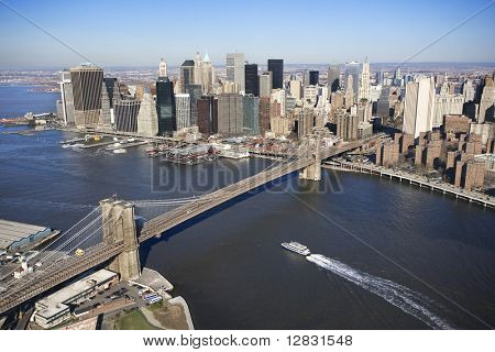 Aerial view of in New York City with  Brooklyn Bridge and Manhattan skyline with ferry boat.