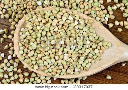 Healthy green buckwheat in a wooden spoon
