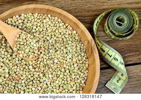 Green buckwheat in a bamboo bowl and centimeter on wooden table