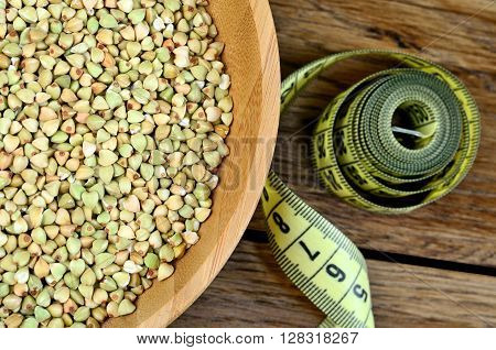 Green buckwheat in a bowl and centimeter on table