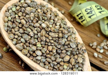 Hemp seeds in a wooden spoon with centimeter on table
