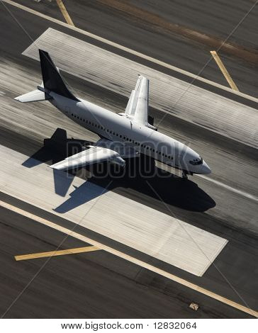 Aerial view of passenger airplane on airport runway.