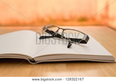 Glasses and opened diary on wood table