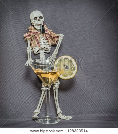Standing human skeleton behind the glass with alcohol fluid and holding car keys in his jaw