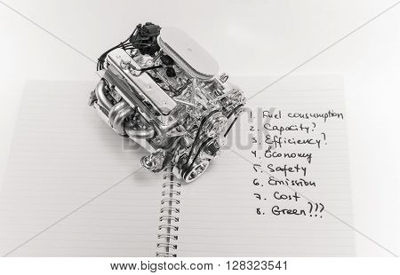 Black and white aluminum truck engine model, standing on open paper notebook with various written words against light-grey background