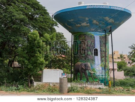 Trichy India - October 15 2013: Tall water tower is painted with a jungle theme showing a water fall and an elephant all against blue background. The tower stands besides green trees.