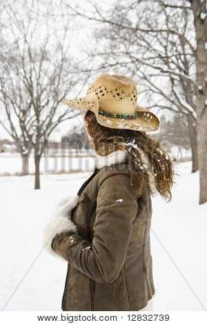 Back view of brunette woman with long hair wearing straw cowboy hat outdoors in the snow.