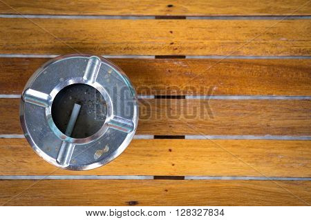 Stainless steel ashtray on wooden desk. smoking concept.