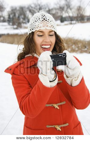 Smiling Caucasian young adult female in winter clothing using digital camera outdoors.