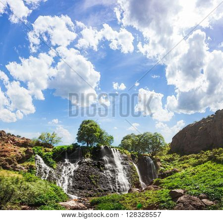 View of beautiful mountain waterfall with blue cloudy sky on background. Exploring Armenia