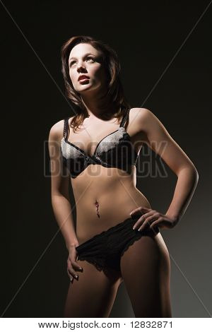 Caucasian woman standing in lingerie with hand on hip.