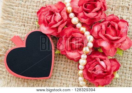 Valentine roses blank red heart gift tag on sack background for your text.