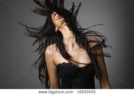 Portrait of pretty young woman flinging long black hair into air.