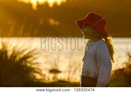 close up of a four year old child wearing a bright red hat standing on the shore of a lake at sunset