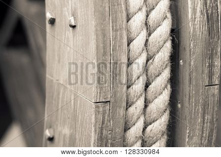 big hempen rope on the old wooden coil a closeup of beige color