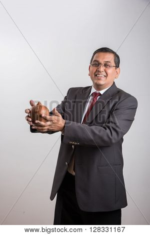 happy indian businessman man holding piggy bank or money box made up of clay, clay money box & asian business man, isolated over white background, indian man with piggy bank, money box