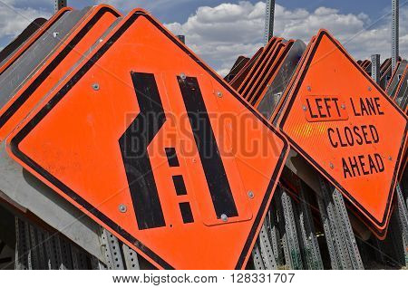 Vertical stacks of orange divided highway and lane closing signs due to road construction
